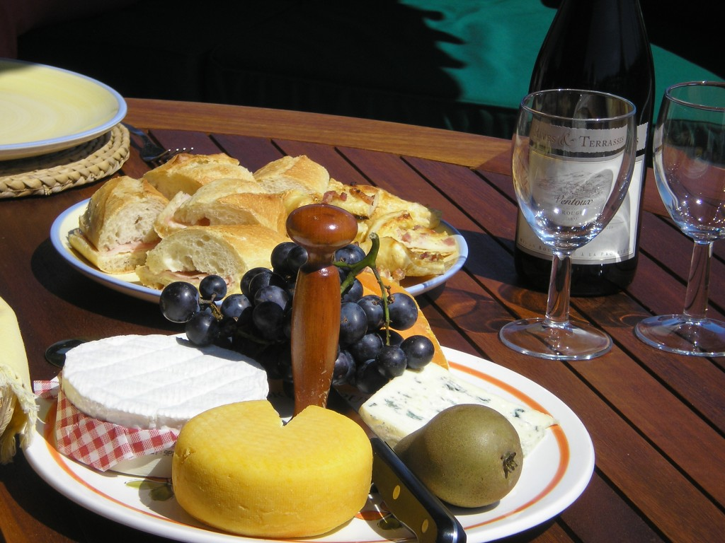A plate of french cheeses, grapes and a bottle of wine on a wodden table
