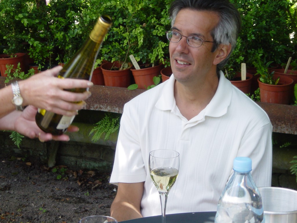 Woman's hands ouring glass of white wine for man