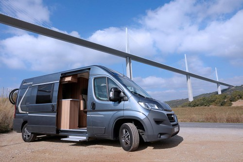 Campervan parked under Millau Viaduct, over the River Tarn, France