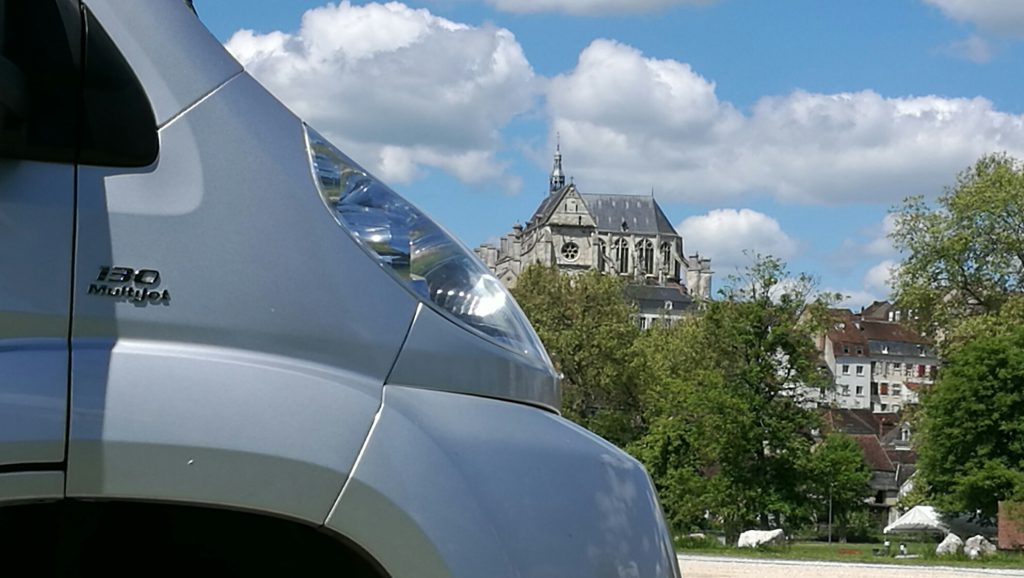 Close up of front of campervan with ancient church at Saint Florentin in background
