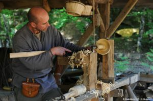 A volunteer turning wood at medieval Guédelon castle
