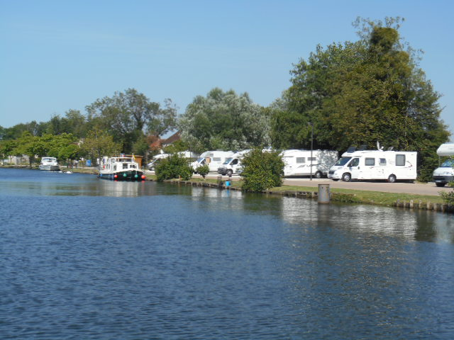 Motorhomes parked at an aire de service next to River Yonne