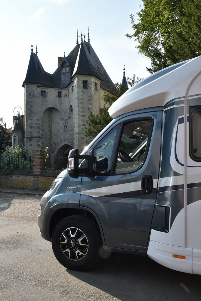 Front end of campervan parked in front of turreted chateau