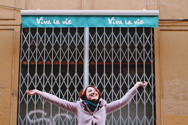 Young woman standing in front of shop called Vive la Vie