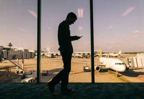 Silhouette of man loking ta his phone with airplane in background