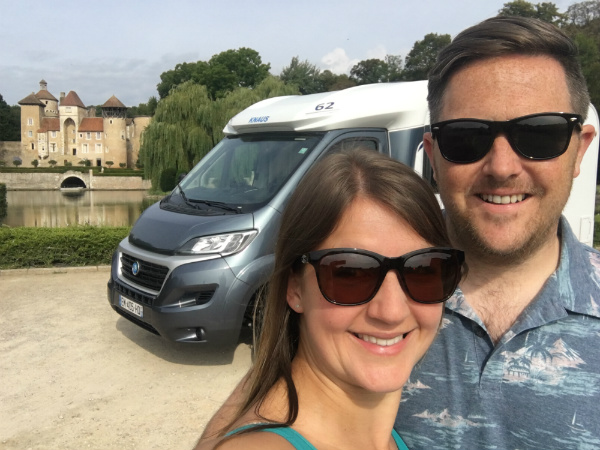 Couple in front of a motorhome and French chateau