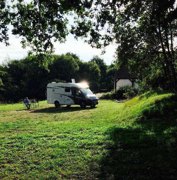 A motorhome parked up for the night in a pretty green field