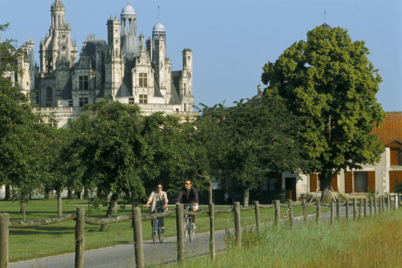 couple cycling near Chambord chateaux