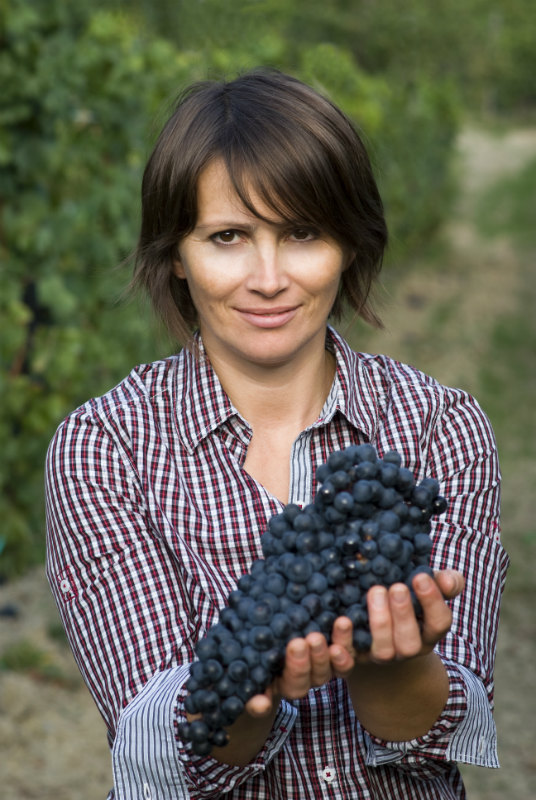 Woman holding huge bunch of black grapes